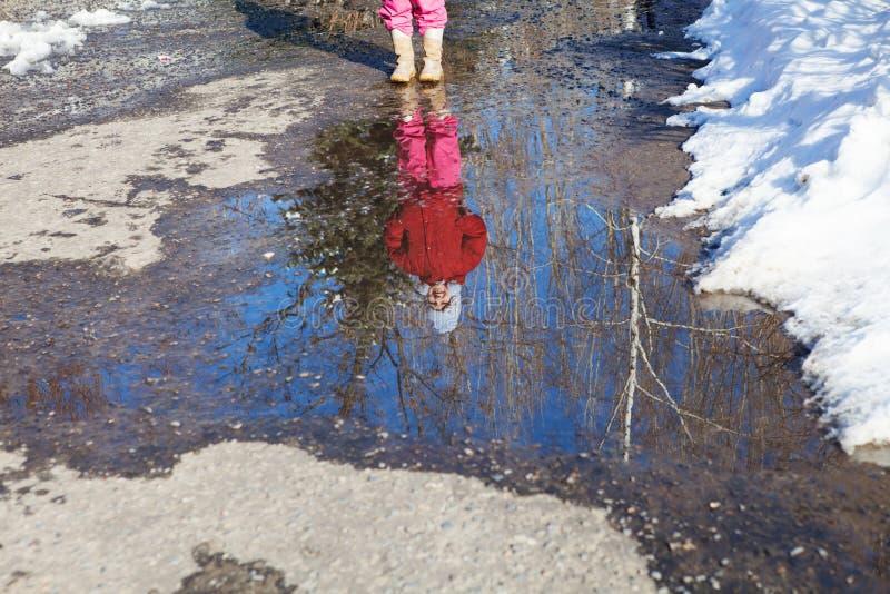Odbicie mała dziewczyna w wiosny kałuży zdjęcie stock