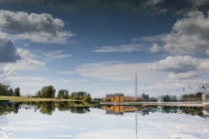 Odbicie na gładkiej powierzchni rzeki budynków, drzew, niebieskiego nieba i chmur. symetria. Przestawny obrazek fotografia stock