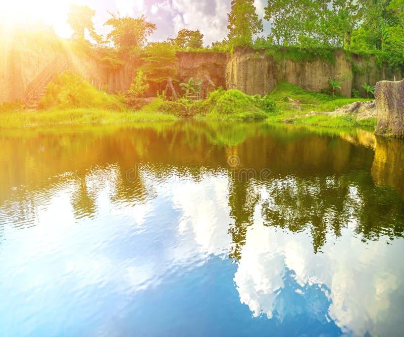 Odbicie niebo, chmura w Błękitne Wody jeziorze z Dużą Rockową falezą Wokoło Go i wzrok Żółty słońce promień fotografia royalty free
