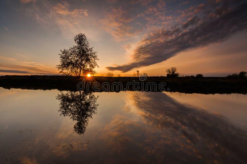 Odbicie piękny jutrzenkowy niebo w rzece obraz royalty free