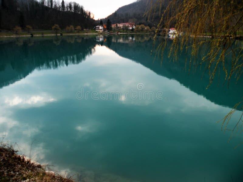 Odbicie wzgórza, góry, wioska i niebo w turquise wodzie, fotografia royalty free