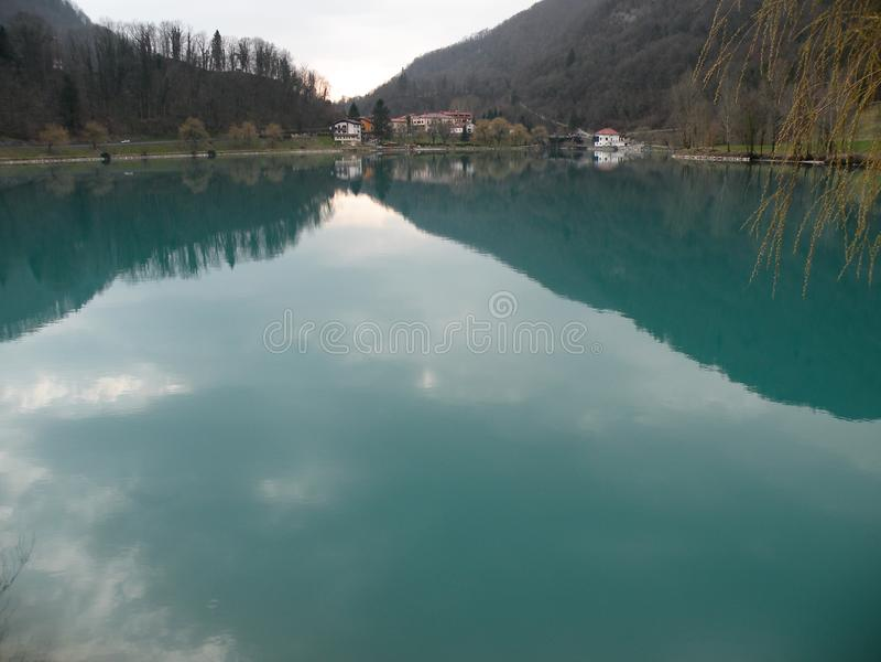 Odbicie wzgórza, góry, wioska i niebo w turquise wodzie, obrazy royalty free