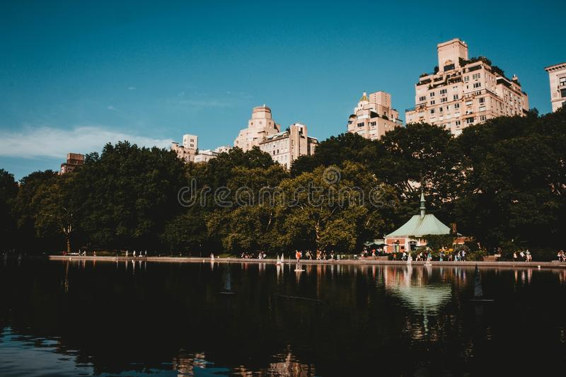 Odbija jezioro w parku z wysokimi budynkami i pi?knym niebem zdjęcia stock
