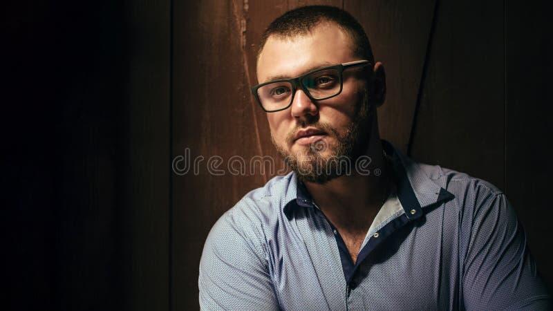 Odbitkowa przestrzeń, twój tekst tutaj, brutalny brodaty mężczyzna z tatuażem na jego ręce, portret mężczyzna w dramatycznym świe zdjęcia stock