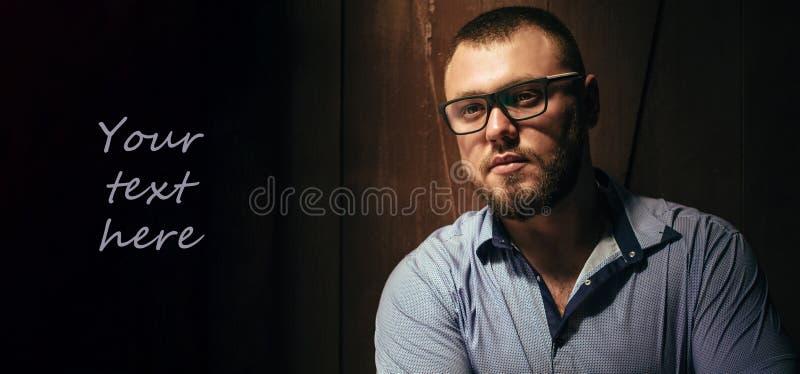 Odbitkowa przestrzeń, twój tekst tutaj, brutalny brodaty mężczyzna z tatuażem na jego ręce, portret mężczyzna w dramatycznym świe zdjęcia royalty free