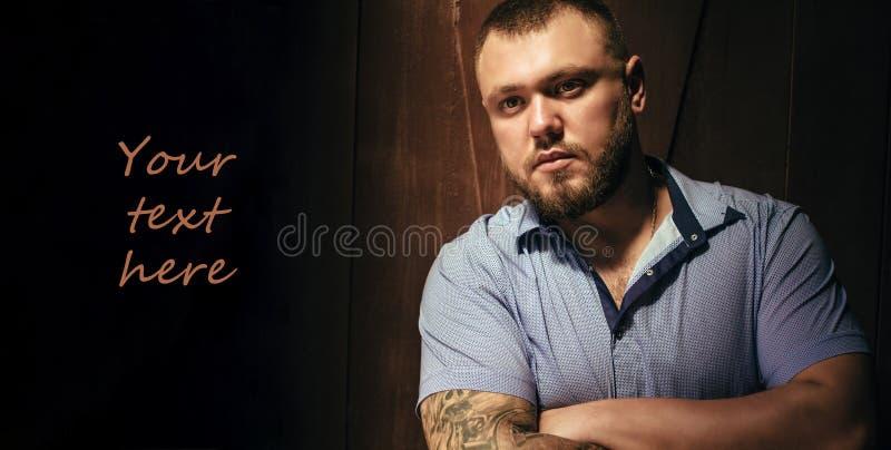 Odbitkowa przestrzeń, twój tekst tutaj, brutalny brodaty mężczyzna z tatuażem na jego ręce, portret mężczyzna w dramatycznym świe obrazy stock