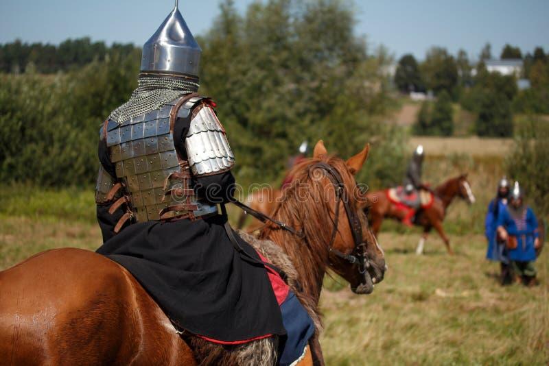 odbudowa Średniowieczny opancerzony rycerz na koniu Equestrian żołnierz w dziejowym kostiumu Reenactor jest w polu fotografia royalty free