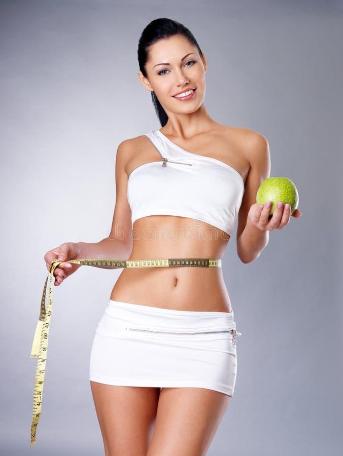 Odchudzająca kobieta z pomiarowym jabłkiem i taśmą obraz stock