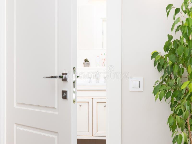 Odchylony biały drzwi łazienka Serie wyłaczają dalej światło - szarość w zdjęcia royalty free