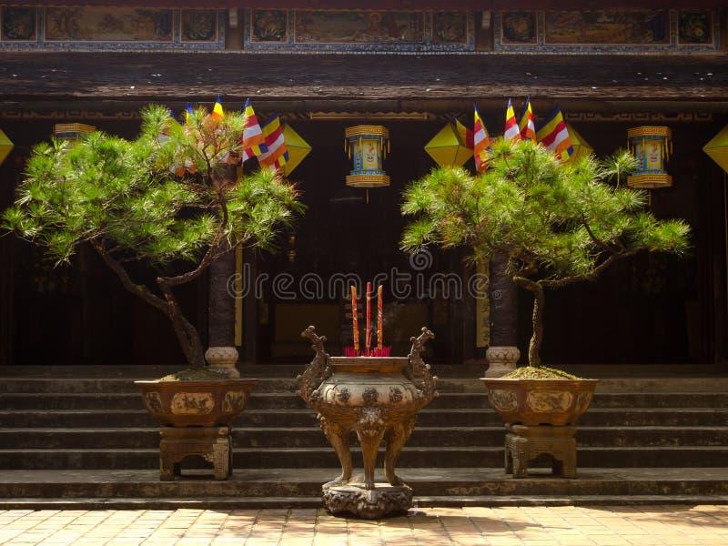 Odcień Wietnam, Wrzesień, - 13 2017: Zamyka up dwa pięknej rośliny w garnki, z niektóre kadzidłami w ogromnym garnku w przodzie zdjęcie royalty free
