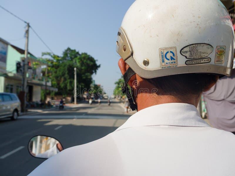 Odcień Wietnam, Wrzesień, - 13 2017: Zamyka up niezidentyfikowany mężczyzna z białym hełmem, jadący motocykl w ulicie wewnątrz obrazy stock