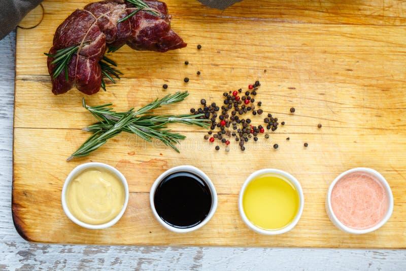 Odcinająca wołowina z ziele i kumberlandami na drewnianej desce obrazy stock
