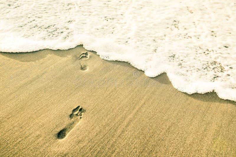 Odciski stopy nagi bosy przy plażą przeciw nadchodzącej fala pianie fotografia stock