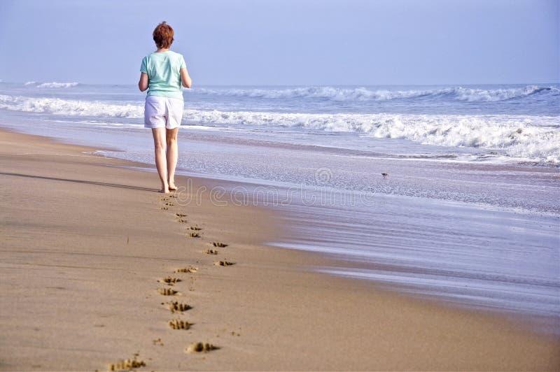 Odciski stopy w piasku Odludnym piechurem fotografia stock