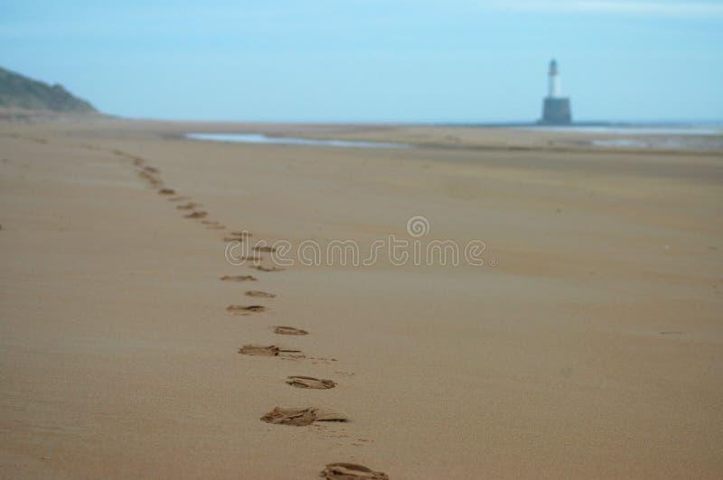 Odciski stopy wzdłuż plaży latarnia morska zdjęcie royalty free