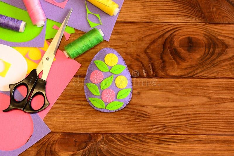 Odczuwany Wielkanocny jajko, szwalni materiały i narzędzia na drewnianym tle z kopią, opróżniamy przestrzeń dla teksta Jaskrawi j zdjęcie royalty free