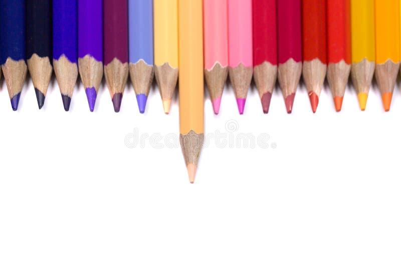 Odd One Out Color Pencil che affronta giù sul fondo bianco puro fotografia stock libera da diritti