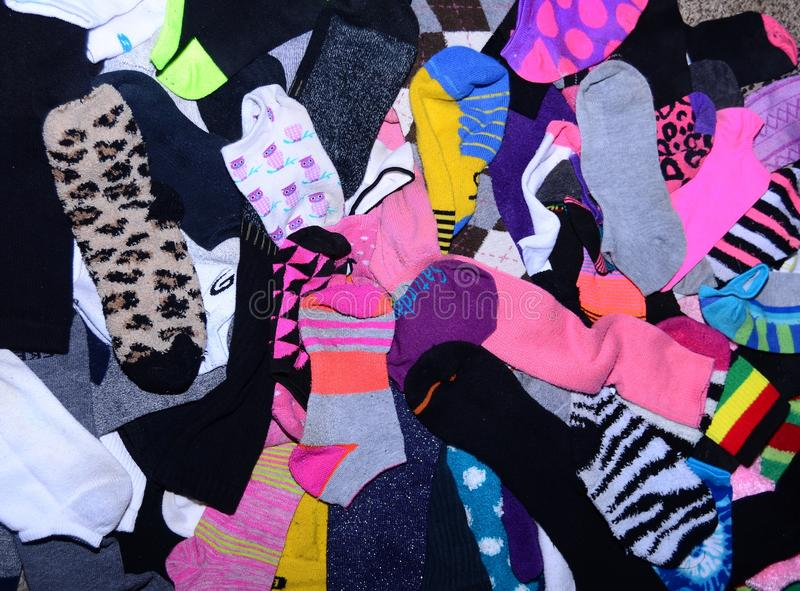 Odd socks. Variety of color, length and material in this mess of mismatched socks stock image