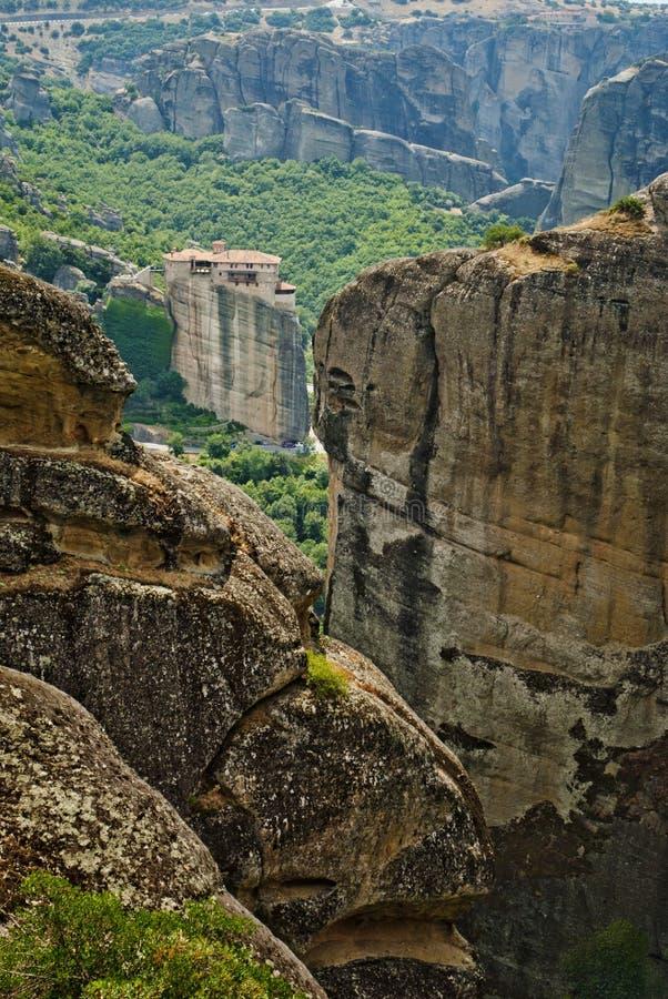 Oddalony widok z monasterem od Grecja z ampuły zieleni ogródem między wysokimi i brown skałami zdjęcie royalty free