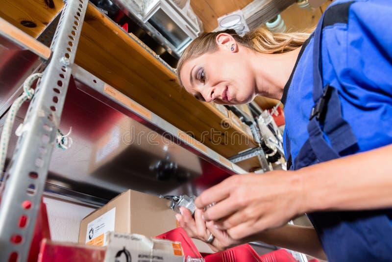 Oddany żeński pracownik sprawdza ilość w magazynie sanitarny artykuły sklep obraz stock