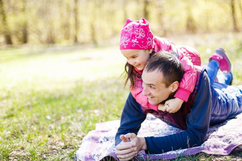 Oddany ojciec i córka leżący na trawie, cieszący się towarzystwem, więzienstwem, bawiący się, bawiący się w naturze w świetle, fotografia royalty free
