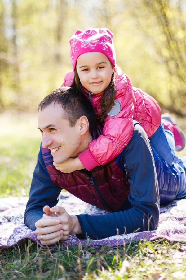 Oddany ojciec i córka leżący na trawie, cieszący się towarzystwem, więzienstwem, bawiący się, bawiący się w naturze w świetle, fotografia stock