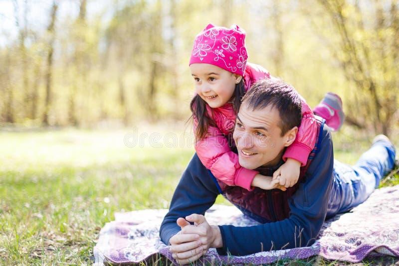 Oddany ojciec i córka leżący na trawie, cieszący się towarzystwem, więzienstwem, bawiący się, bawiący się w naturze w świetle, obraz royalty free