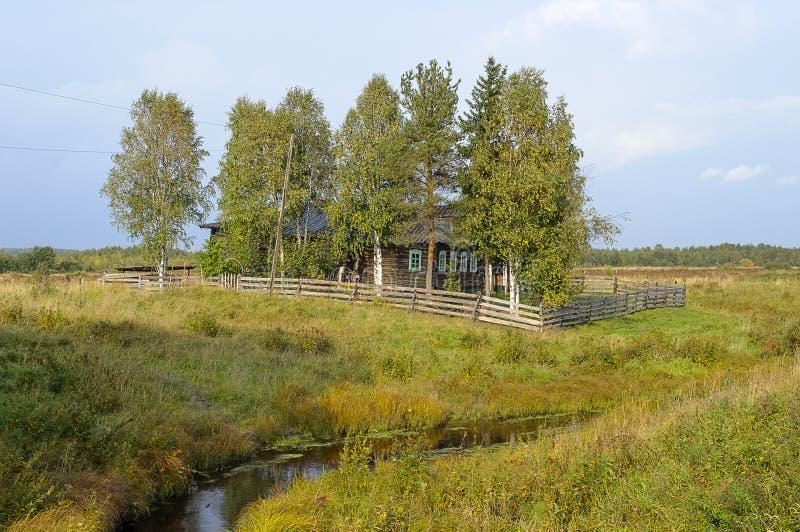 Oddzielny stary dom z drewnianym ogrodzeniem w wiosce zdjęcia stock