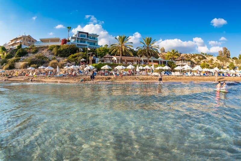 Odefinierbart folk som kopplar av på Coral Bay Beach, en av den mest berömda stranden royaltyfri bild