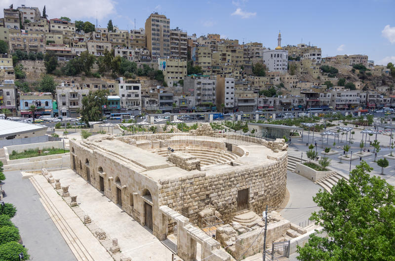 Odeon - pouco anfiteatro romano dentro na cidade com citysca de Amman fotos de stock royalty free