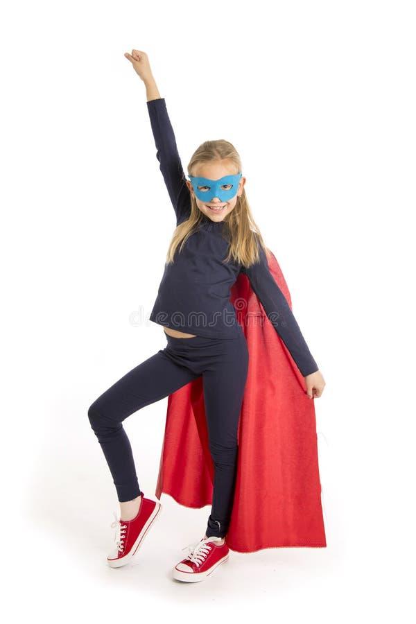7 oder 8 Jahre altes junges weibliches Schulmädchenkind, bei der Superheld-Kostümausführung glücklich und aufgeregtes lokalisiert lizenzfreie stockfotografie