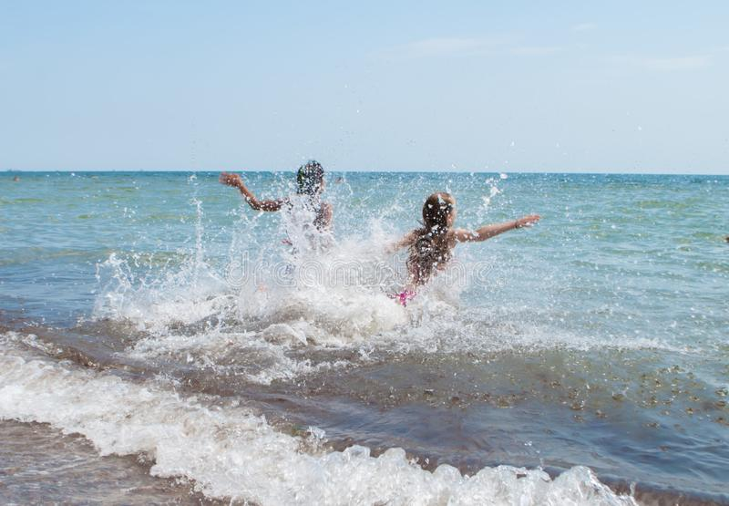 Teenagers running into the sea to swim in a summer camp. Odesa rgn. Ukraine, August 7, 2018: Teenagers running into the sea to swim in a summer camp royalty free stock photos