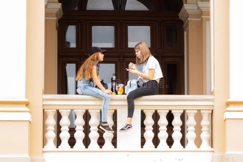 odessa Украина 2018 07 26 2 девушки сидят на парапете оперного театра и говорят в реальном маштабе времени стоковое фото rf