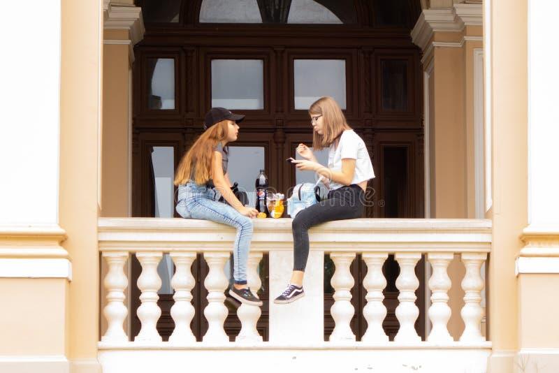 odessa l'ucraina 2018 07 26 Due ragazze stanno sedendo sul parapetto del teatro dell'opera e stanno parlando vivacemente fotografia stock libera da diritti