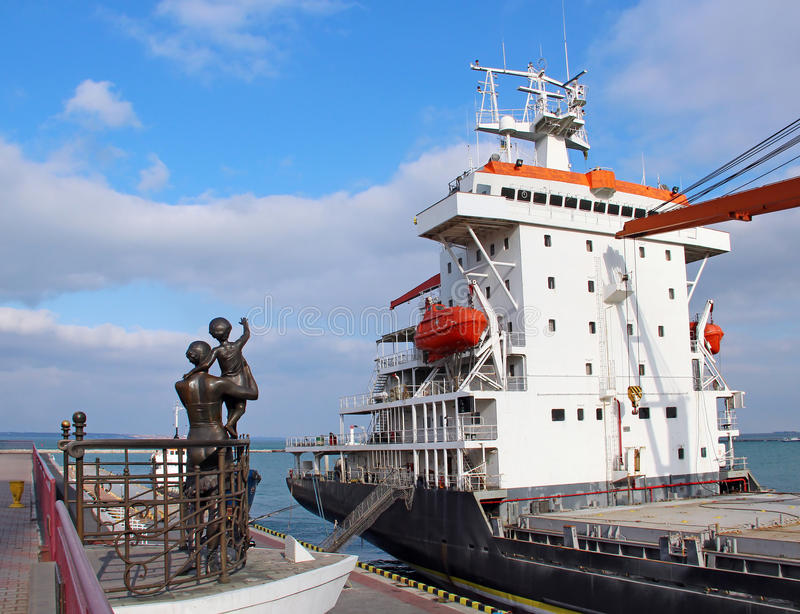 Odessa port, Ukraine. Cargo ship and Monument to Sailor's Wife in Odessa Port, Ukraine stock photo