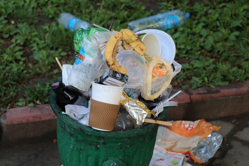 Odessa, Ucr?nia Em junho de 2019 Lata de lixo completa, com o lixo colocado na terra imagem de stock
