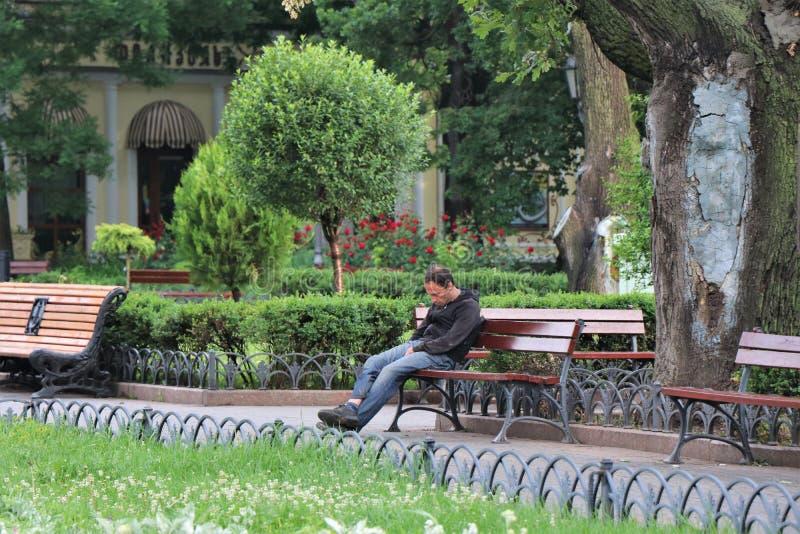 Odessa, Ucr?nia Um sono desabrigado em um banco de parque público imagem de stock