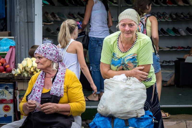 ODESSA UKRAINA - AUGUSTI 13, 2015: Gammal kvinna som säljer grönsaker på den Privoz marknaden, den huvudsakliga marknaden av Odes royaltyfria bilder