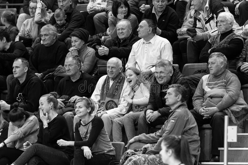 ODESSA, UKRAINA - CIRKA, 2020: Spectators in stands of gym during game of their favorite teams. Sports fans and spectators in stock photography