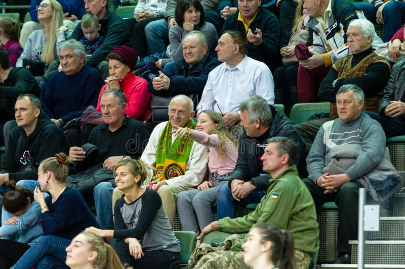 ODESSA, UKRAINA - CIRKA, 2020: Spectators in stands of gym during game of their favorite teams. Sports fans and spectators in stock photos