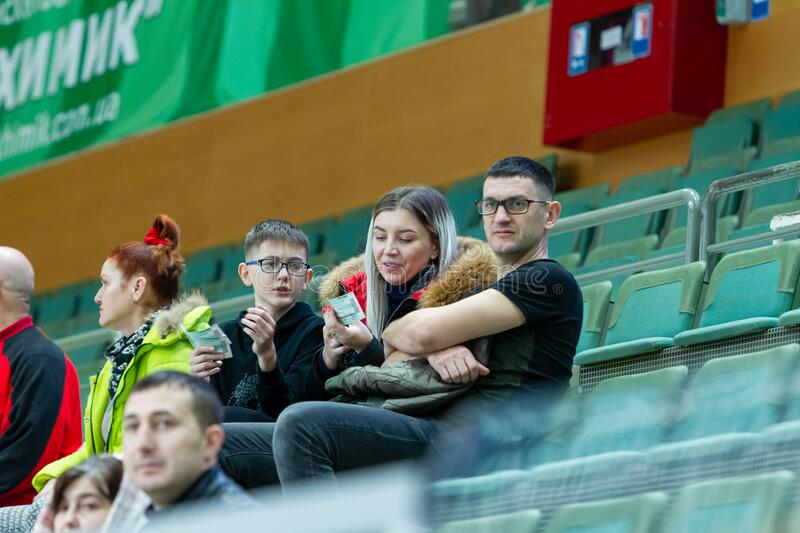 ODESSA, UKRAINA - CIRKA, 2020: Spectators in stands of gym during game of their favorite teams. Sports fans and spectators in stock photo