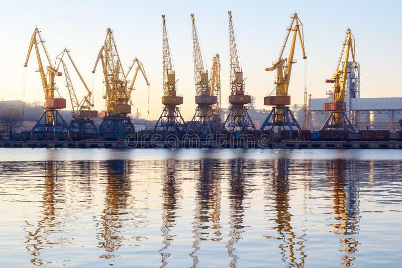 Odessa Ukraina - Januadry 02, 2017: Behållarekranar i lastportterminal, lastkranar reflekterade i vatten Solnedgång arkivbilder