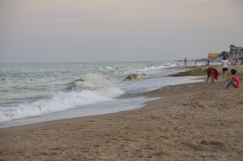 Odessa Ukraina - Juli 29, 2014: Oidentifierat folk som kopplar av på den sandiga stranden av Blacket Sea i Odessa royaltyfri foto