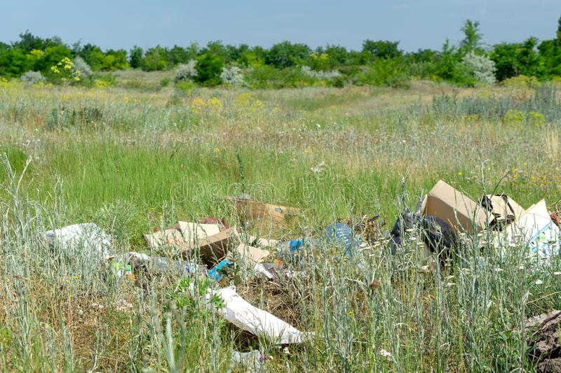 Odessa Ukraina - Juni 08, 2019: Avskräde spridd i fältet nära skogföroreningen av naturen arkivbild