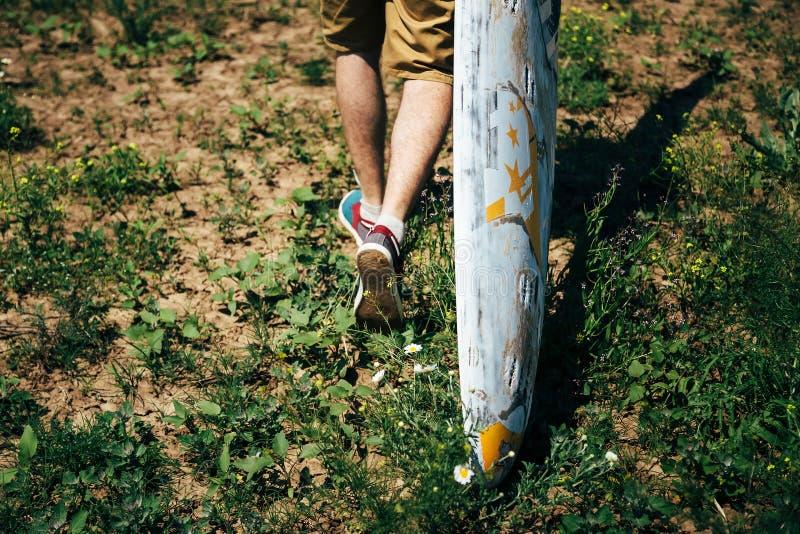 ODESSA UKRAINA -, MAY 20 2015: Den unga surfaren med en gammal surfingbräda är på hans väg till stranden royaltyfria foton