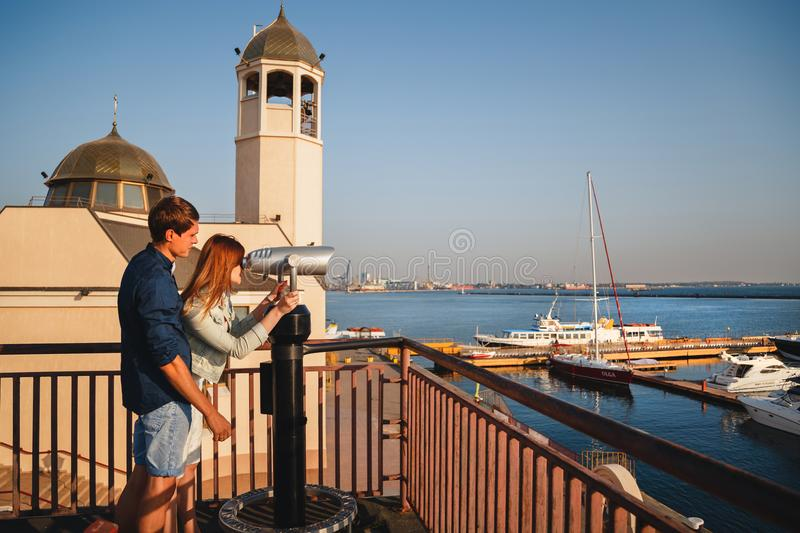 ODESSA, UKRAINE - AUGUST 06, 2015: Happy romantic attractive young couple looking at Hi Spy Viewing Machine, binoculars from the w stock image