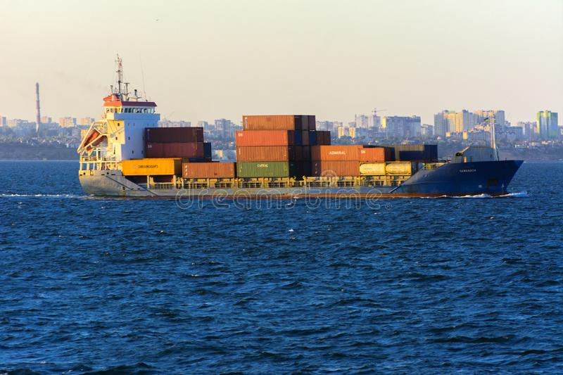 Odessa, Ukraine - August 08, 2018. A large cargo ship transports. Containers in the open sea in the evening soft sunlight against a blue sky. The concept of royalty free stock photo