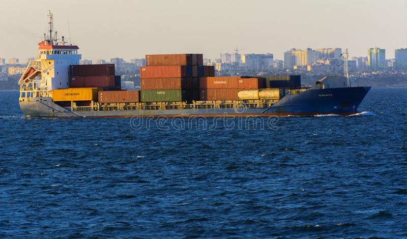 Odessa, Ukraine - August 08, 2018. A large cargo ship transports. Containers in the open sea in the evening soft sunlight against a blue sky. The concept of stock photos