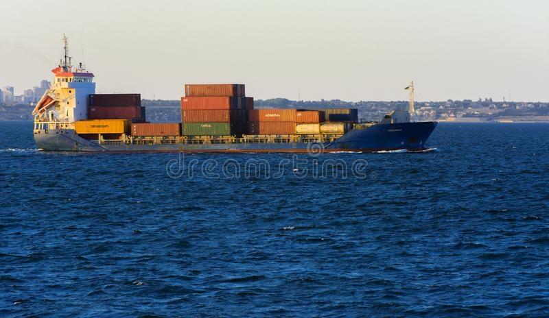 Odessa, Ukraine - August 08, 2018. A large cargo ship transports. Containers in the open sea in the evening soft sunlight against a blue sky. The concept of royalty free stock photography