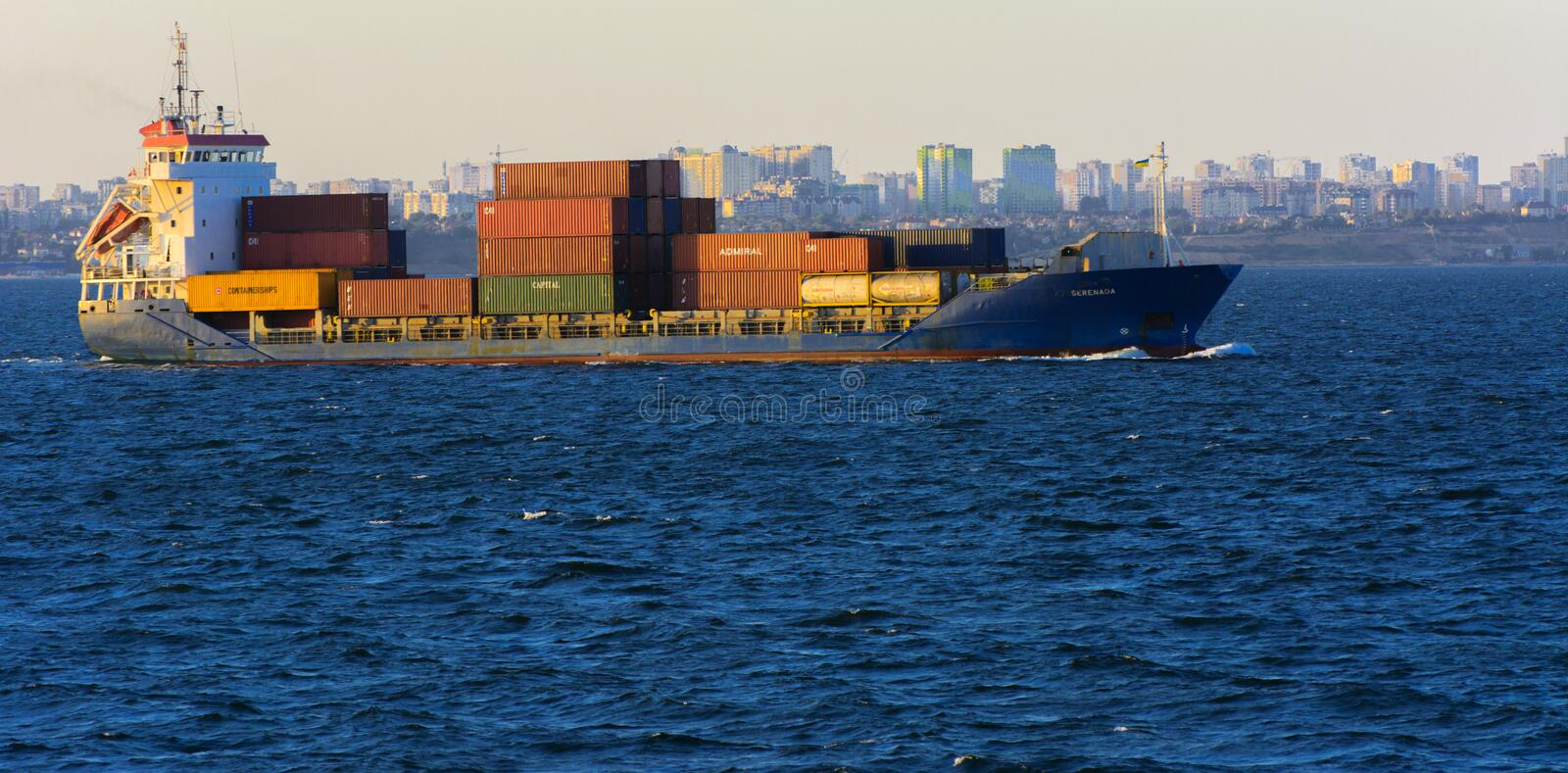 Odessa, Ukraine - August 08, 2018. A large cargo ship transports. Containers in the open sea in the evening soft sunlight against a blue sky. The concept of stock images